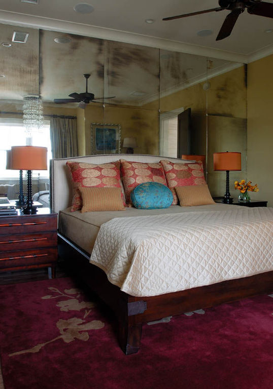 Eclectic master bedroom with antiqued mirror wall panels